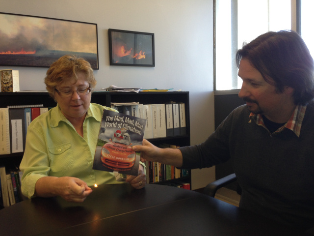 "The original caption published online: This week we received a deluge of free books from the Heartland Institute {this or this }. The book is entitled ""The Mad, Mad, Made World of Climatism"". SHown above, Drs. Bridger and Clements test the flammability of the book."