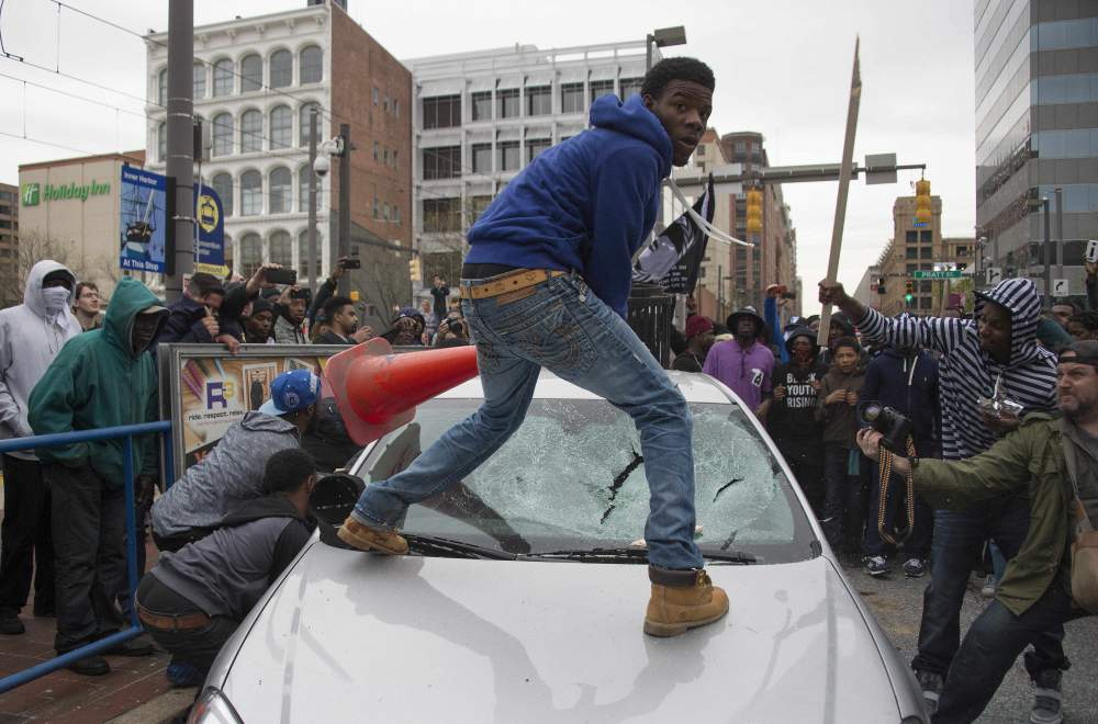TOPSHOTS Demonstrators destroy the windshield of a Baltimore Police car as they protest the death Freddie Gray, an African American man who died of spinal cord injuries in police custody, in Baltimore, Maryland, April 25, 2015. Protesters returned to Baltimore's streets Saturday to vent outrage over the death of Gray on April 12.      AFP PHOTO/JIM WATSONJIM WATSON/AFP/Getty Images ORG XMIT: 550492749 ORIG FILE ID: 540116264